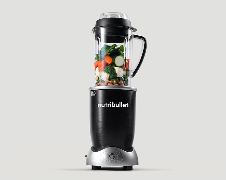 NutriBullet Rx with vegetables and beans on grey background.