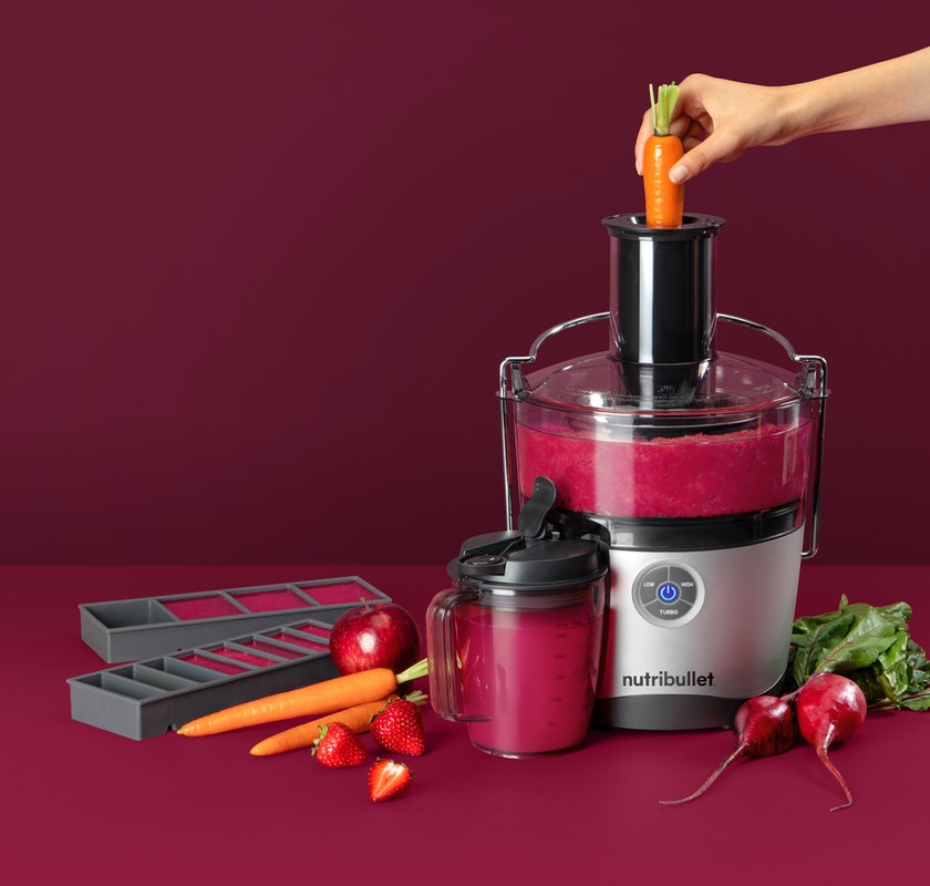 In use NutriBullet Juicer Pro with accessories and various fruits and vegetables.