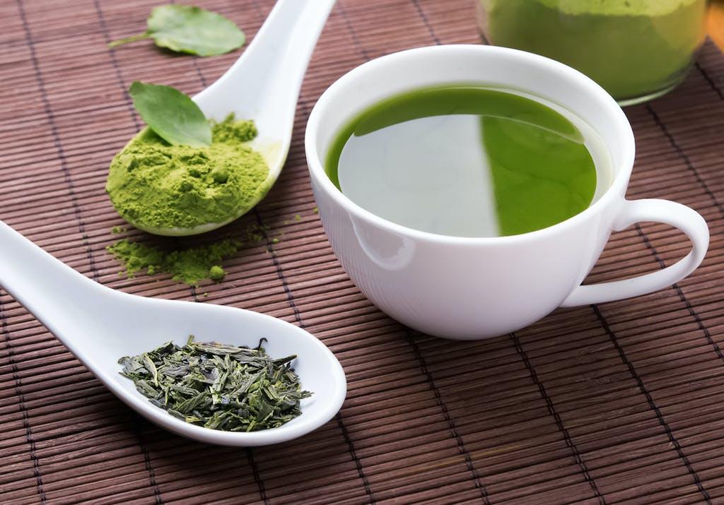 green tea in mug with sencha and matcha in spoons