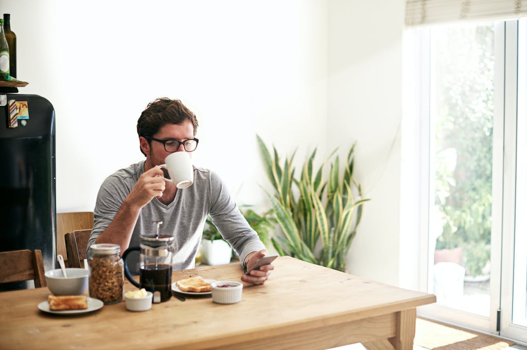 man drinking morning cup of coffee at breakfast dining table