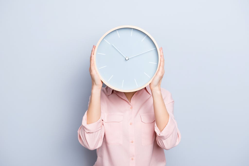 woman in pink shirt holding a clock with blue face