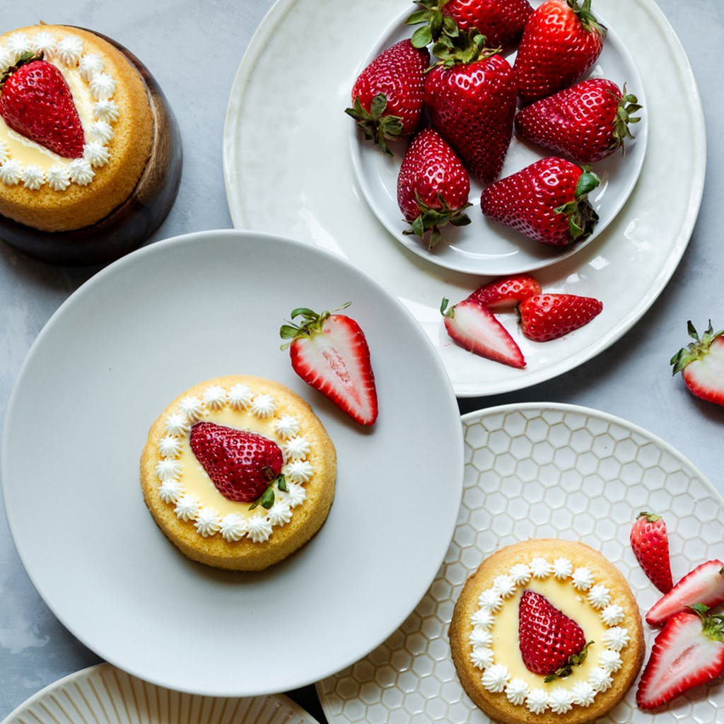 a bowl of strawberries next to mini yellow cakes topped with frosting and strawberries