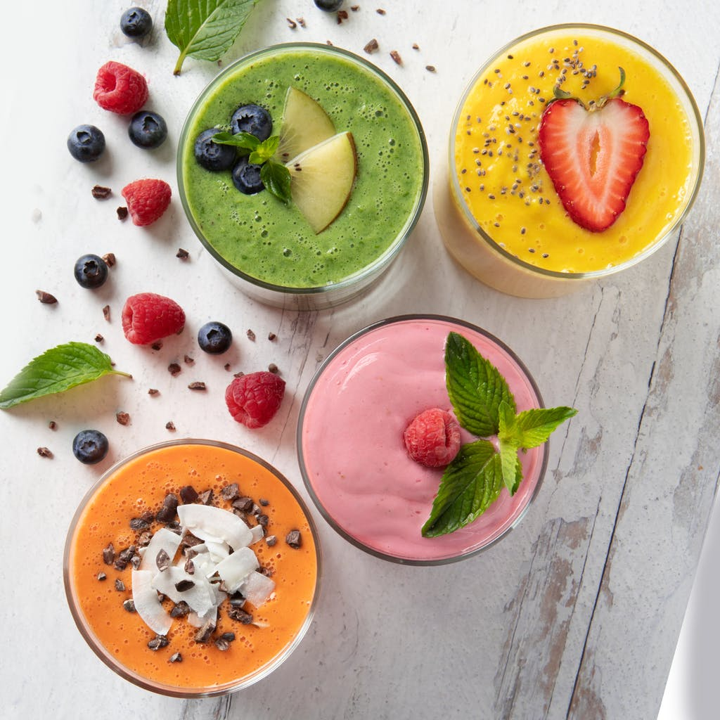 flatlay of orange, pink, yellow, and green smoothies