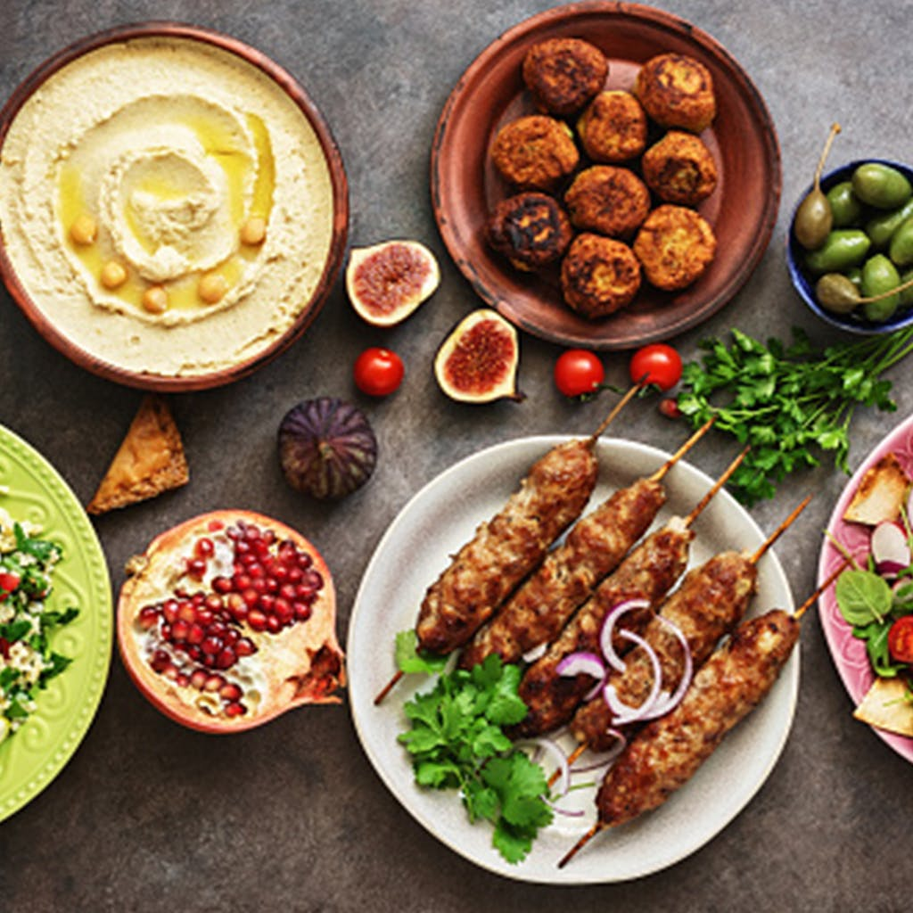 a spread of mediterranean foods including hummus, falafels, and kabobs