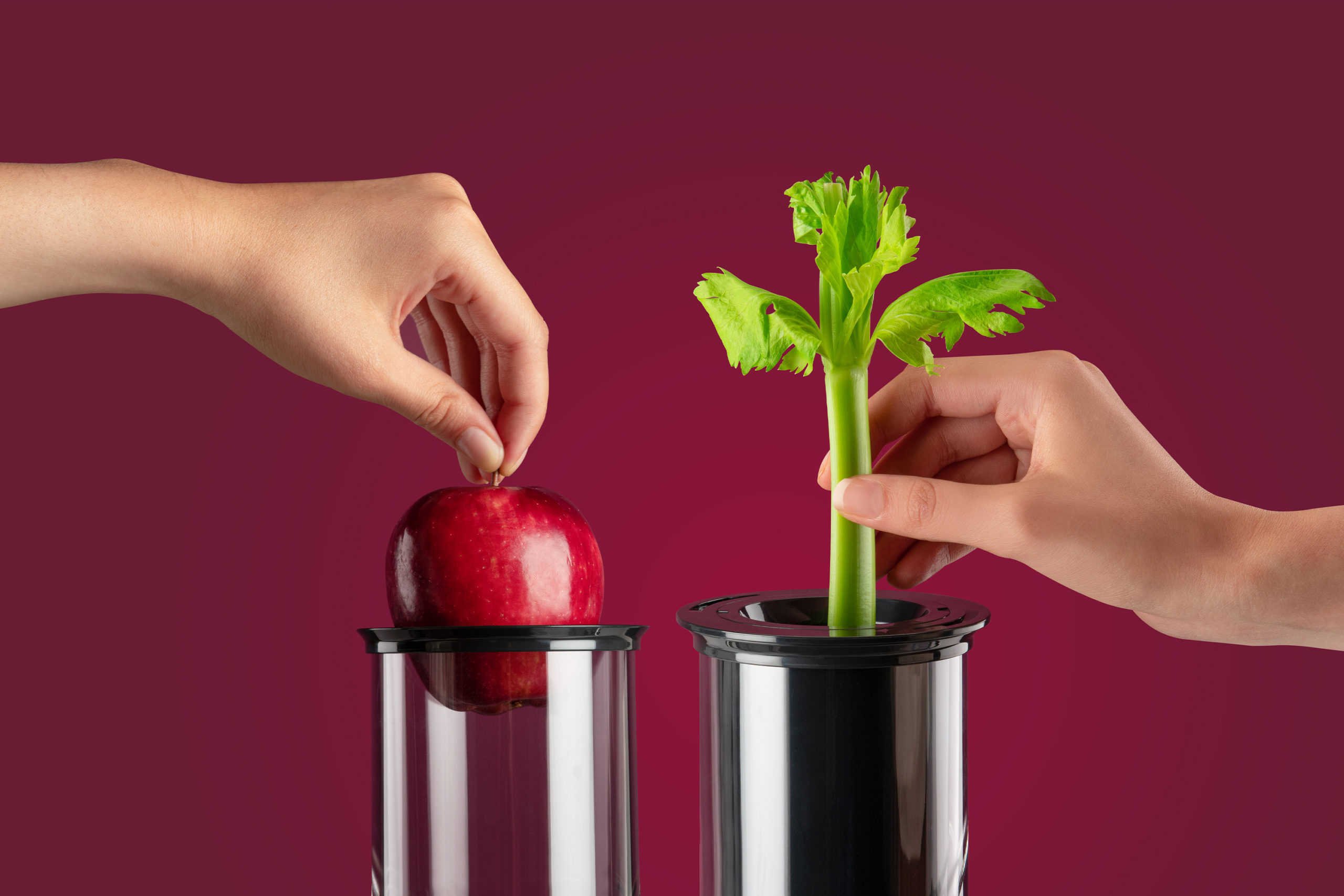 an apple and celery stalk being inserted into the nutribullet Juicer chutes