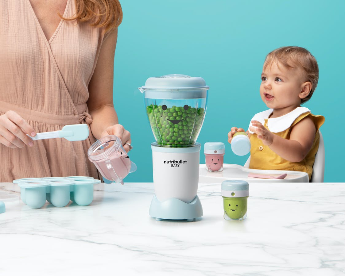 NutriBullet Baby with peas on blue background.