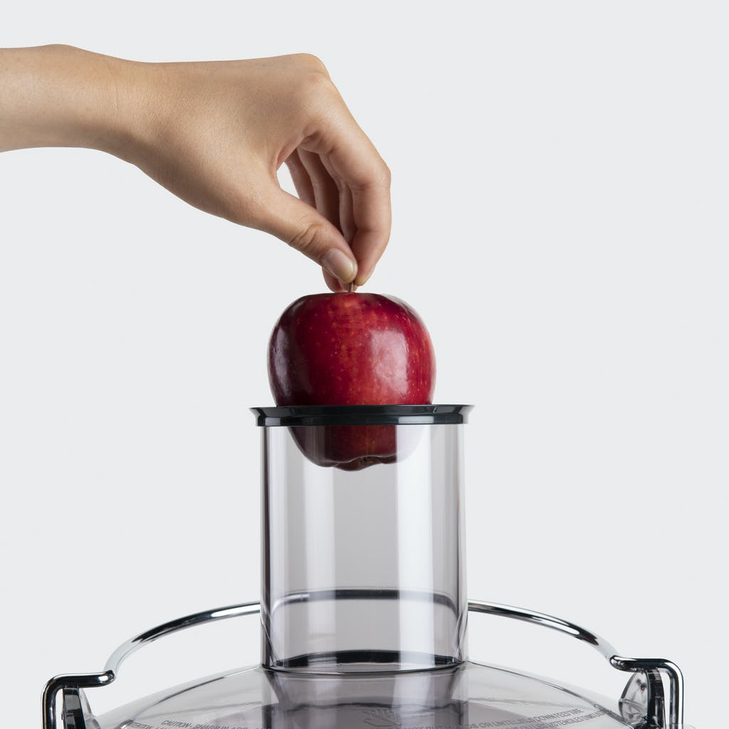 hand adding a red apple to the nutribullet juicer chute