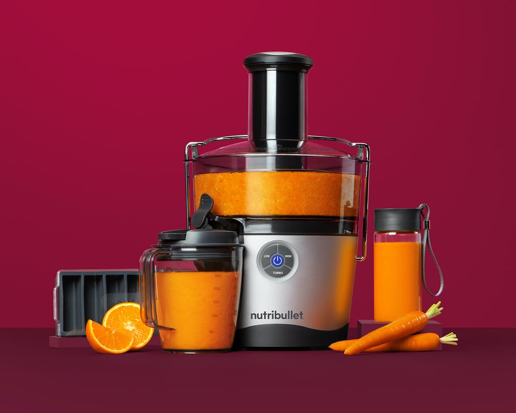 NutriBullet Juicer Pro and accessories with oranges and carrots