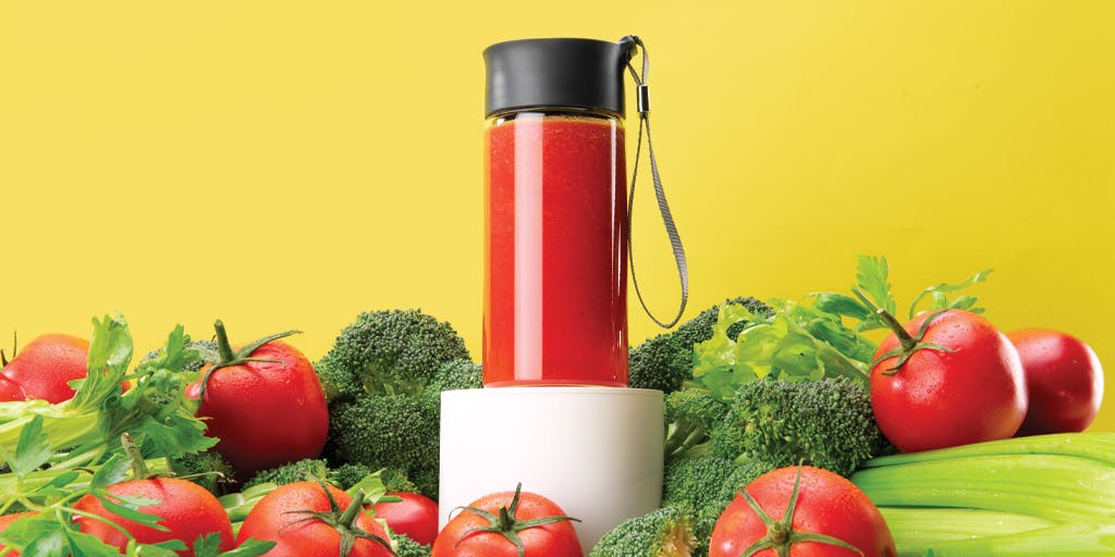 vegetable juice in a to-go bottle surrounded by tomatoes, broccoli, and celery
