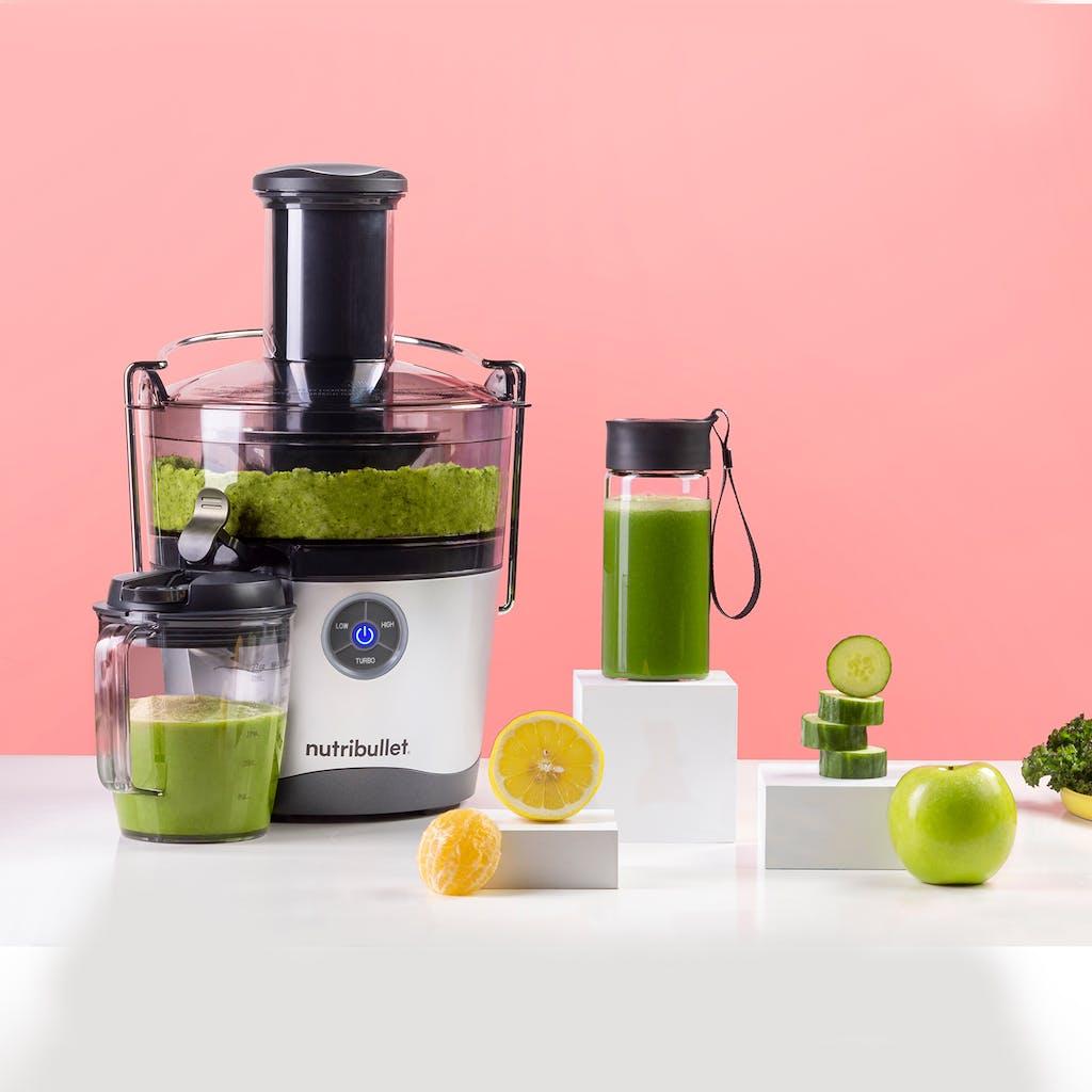 fresh green juice in NutriBullet Juicer on pink background