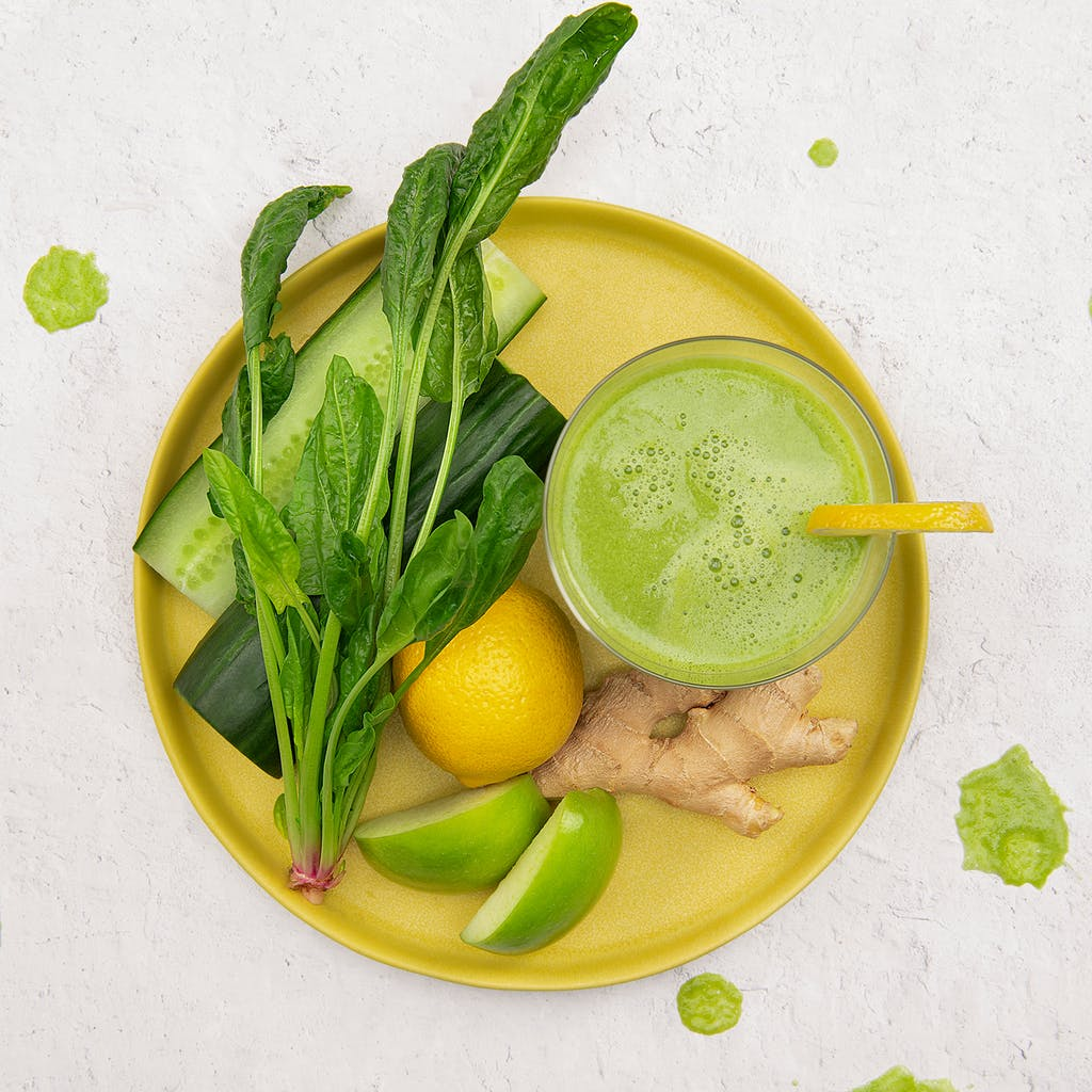 fresh green juice with ginger, lemon, lime, and leafy greens
