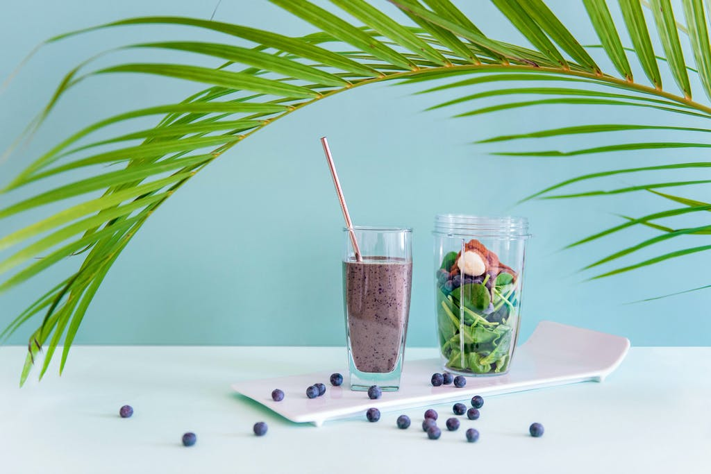 blueberry forever smoothie with spinach and berries on blue background
