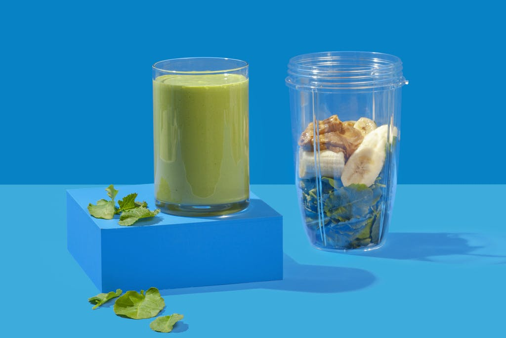 green smoothie in a glass with spinach, banana, and nut butter in NutriBullet cup