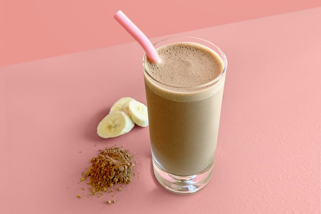 cup of chocolate peanut butter smoothie with banana and cacao powder