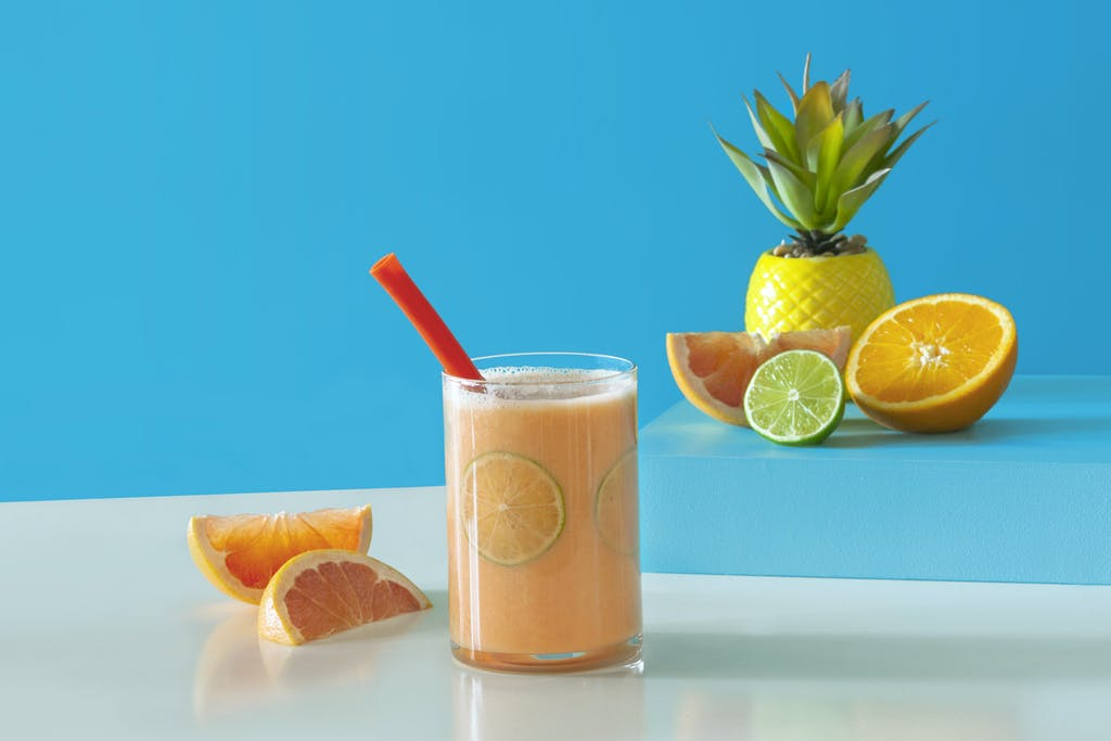 orange smoothie with lime slices in a glass surrounded by cut grapefruit, orange, and lime