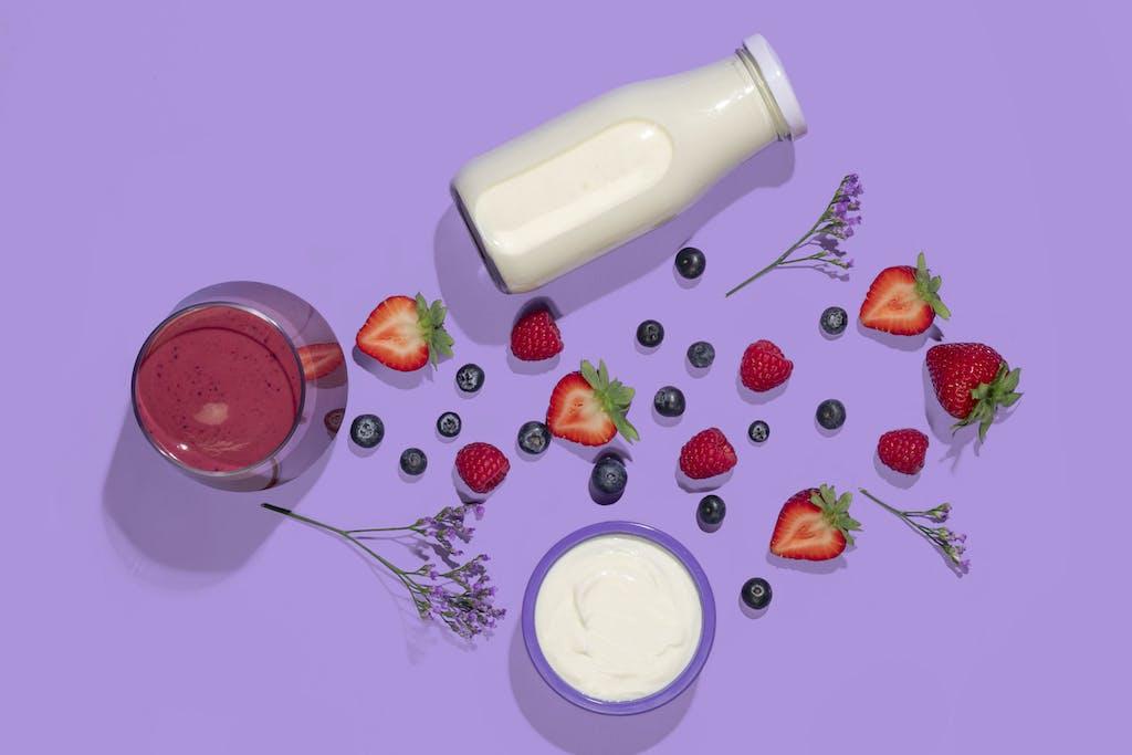 berry smoothie flatlay with strawberries, blueberries, yogurt, and almond milk