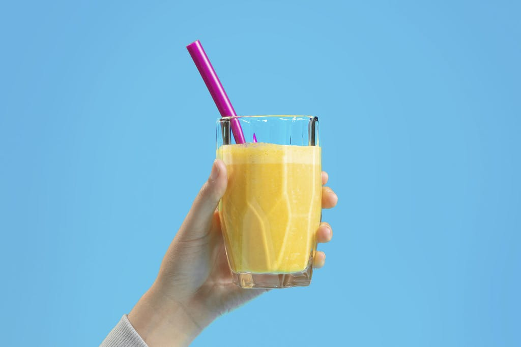 hand holding up a glass of vibrant yellow tropical smoothie