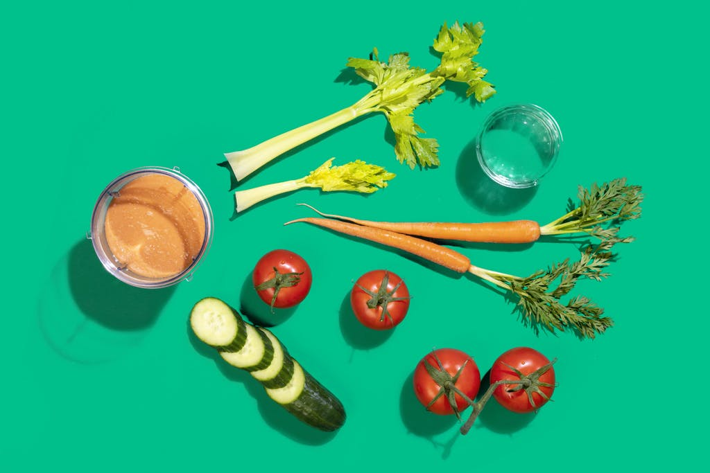 orange vegetable smoothie flatlay with celery, tomatoes, carrots, and cucumber