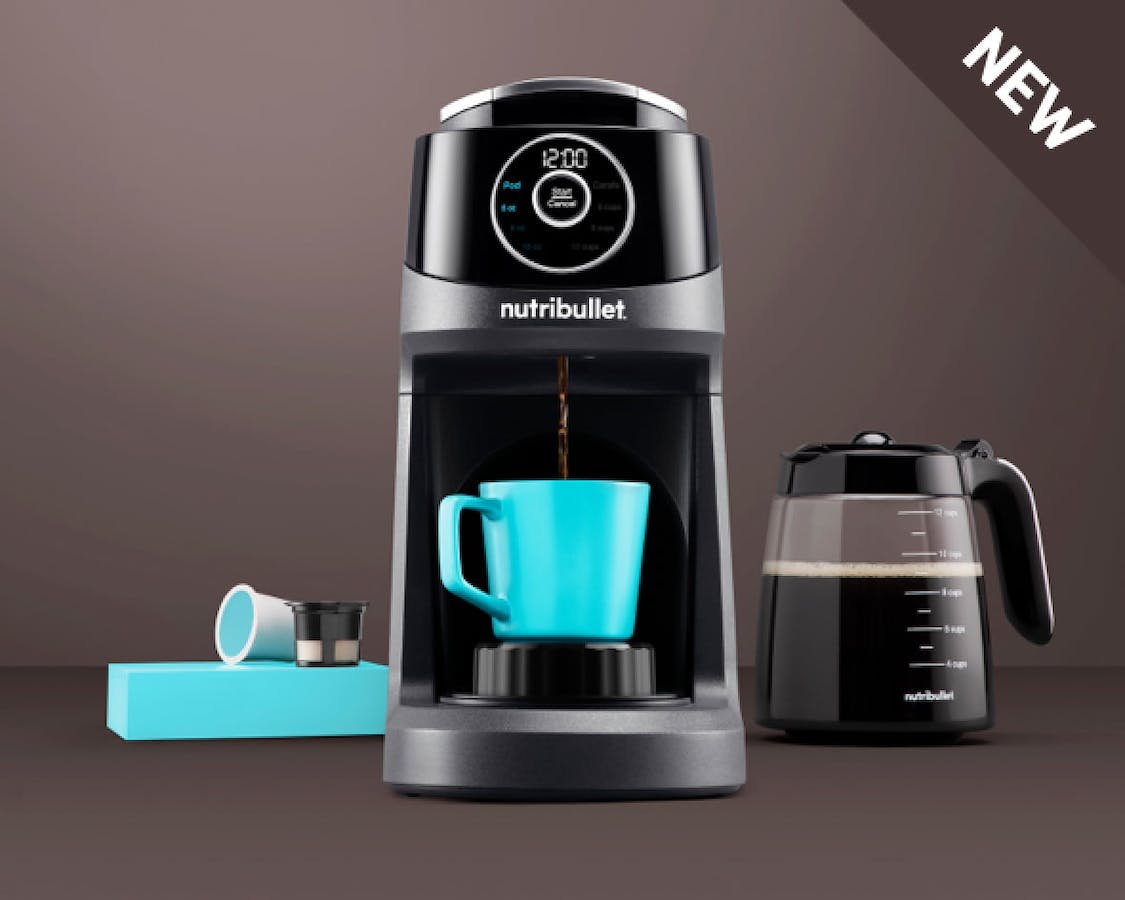 NEW Brew Choice machine making coffee in blue mug with carafe, pods beside it on brown background.
