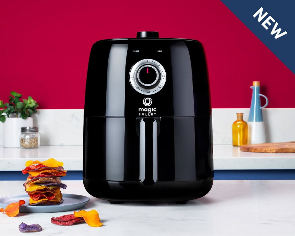 NEW Black NutriBullet Magic Bullet Air Fryer next to chips on kitchen counter with pink background.