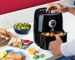 Product preview 2 of 9. Thumbnail of hands using the black air fryer to make curly fries with different foods on counter.
