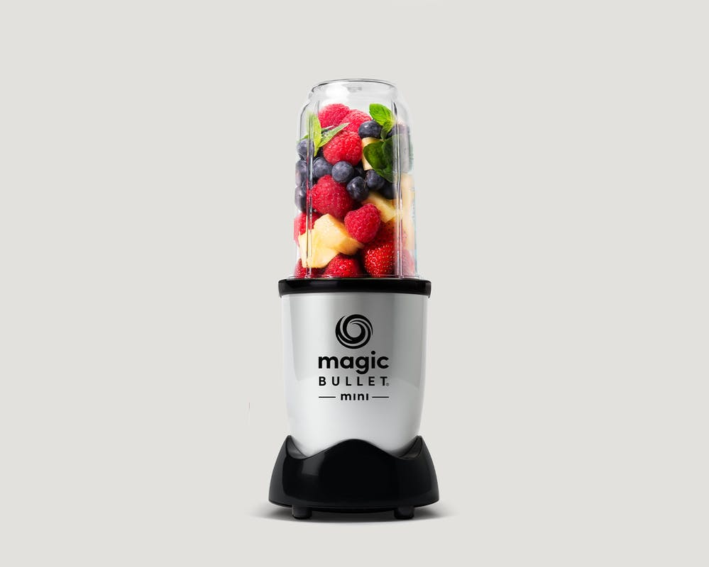 Magic Bullet Mini filled with fruit on gray background