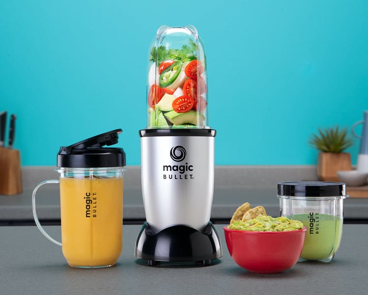 Magic Bullet with vegetables and cups of smoothies and bowl of guacamole on blue background.