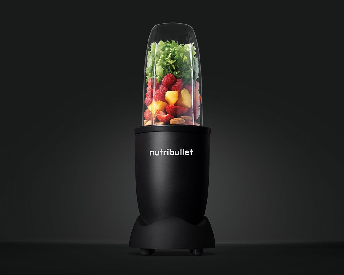 NutriBullet Pro Exclusive! with fruits, vegetables, and nuts on black background.