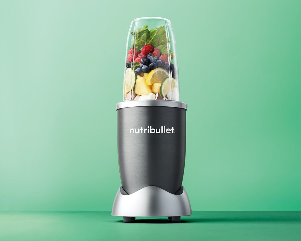 NutriBullet original with fruit and vegetables on green background.