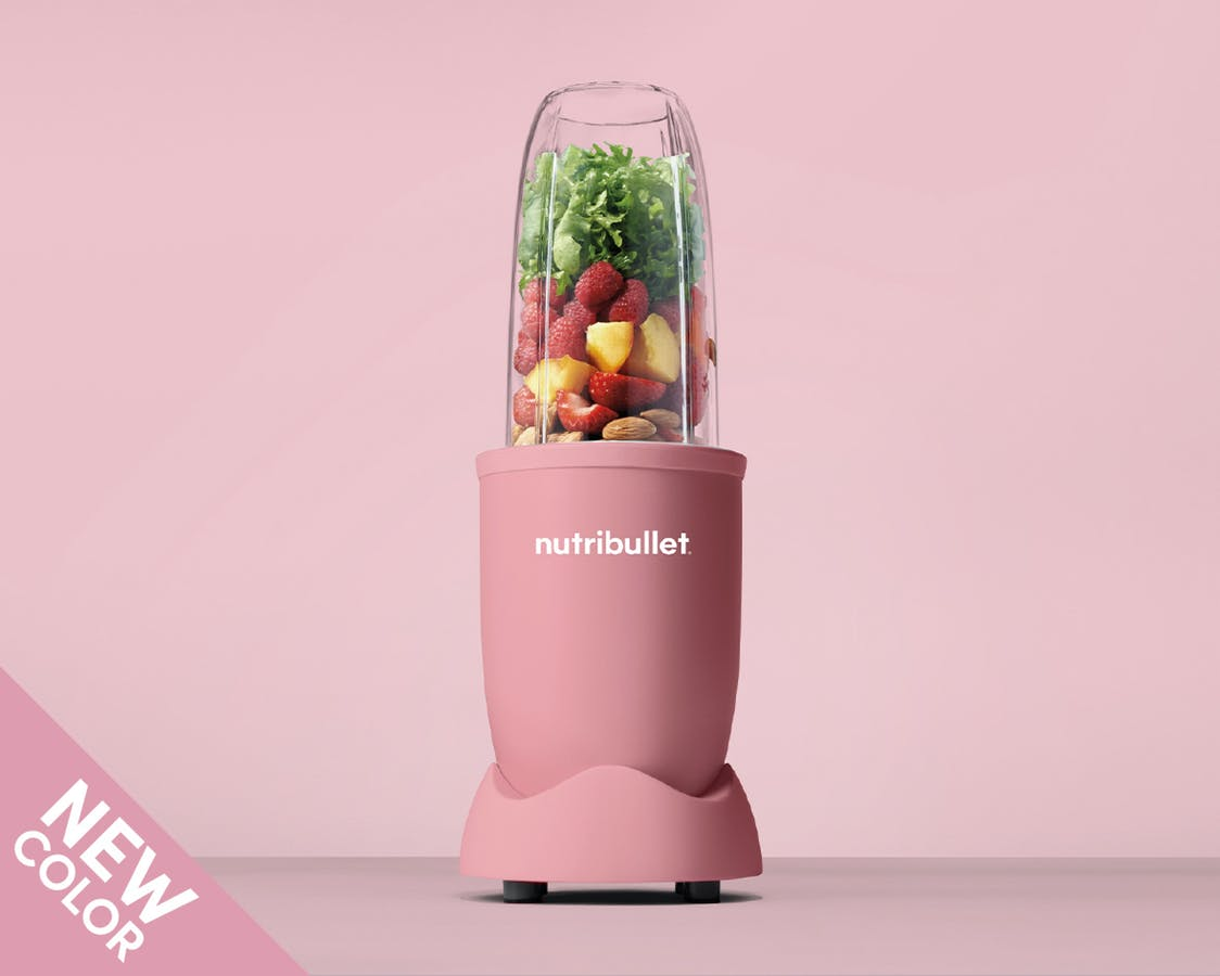 Matte Pink NutriBullet Pro Exclusive! with fruits, vegetables, and nuts on pink background.