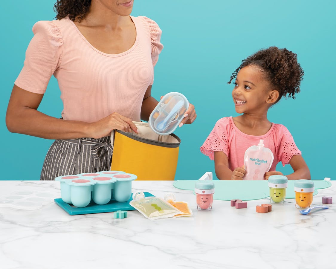 Woman with young girl with assorted NutriBullet Baby products with a blue background.