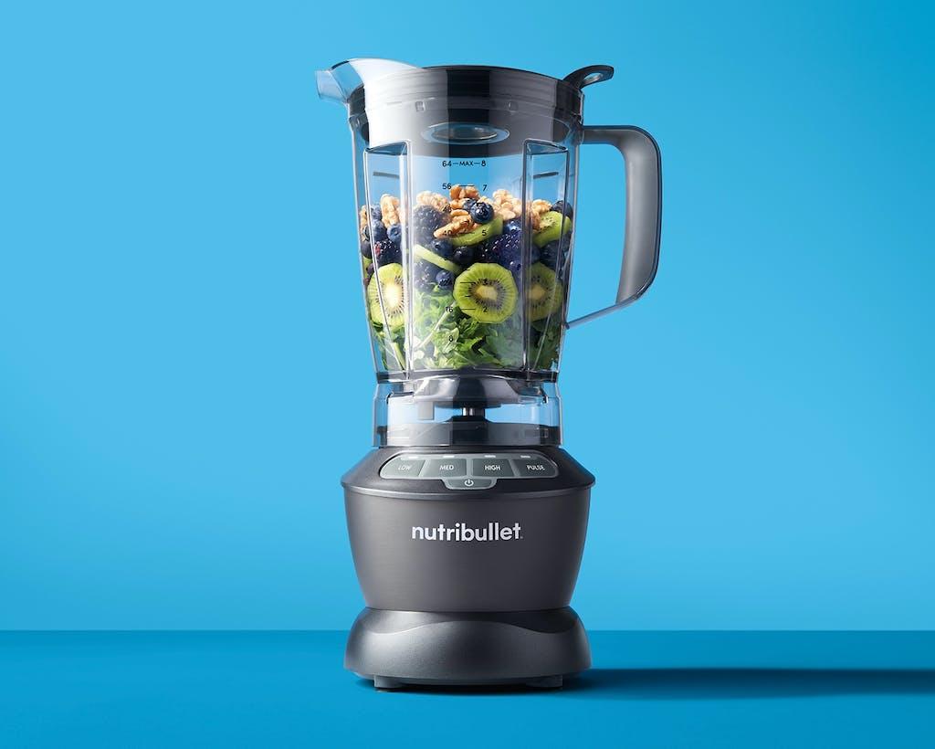 NutriBullet Blender with fruits, vegetables, and nuts on blue background.
