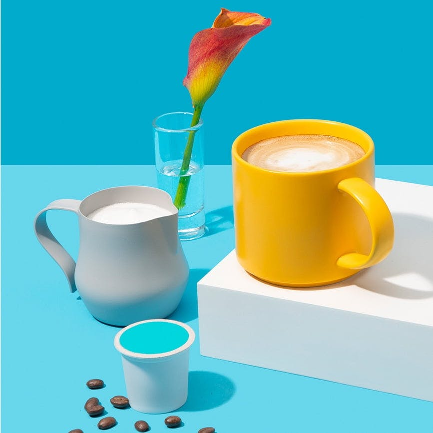 Yellow coffee mug, grey cup of milk, container of coffee grounds and flower vase on blue background.