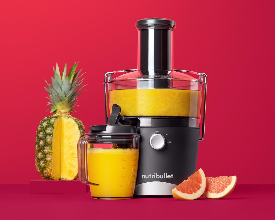 NutriBullet Juicer with pineapple and grapefruit on red background.