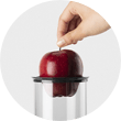 Hand placing red apple into juicer chute