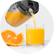 Pitcher pouring orange juice into a glass next to sliced oranges