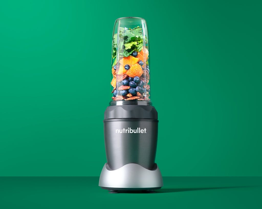 NutriBullet PRO 1000 with fruits, vegetables, and nuts on green background.