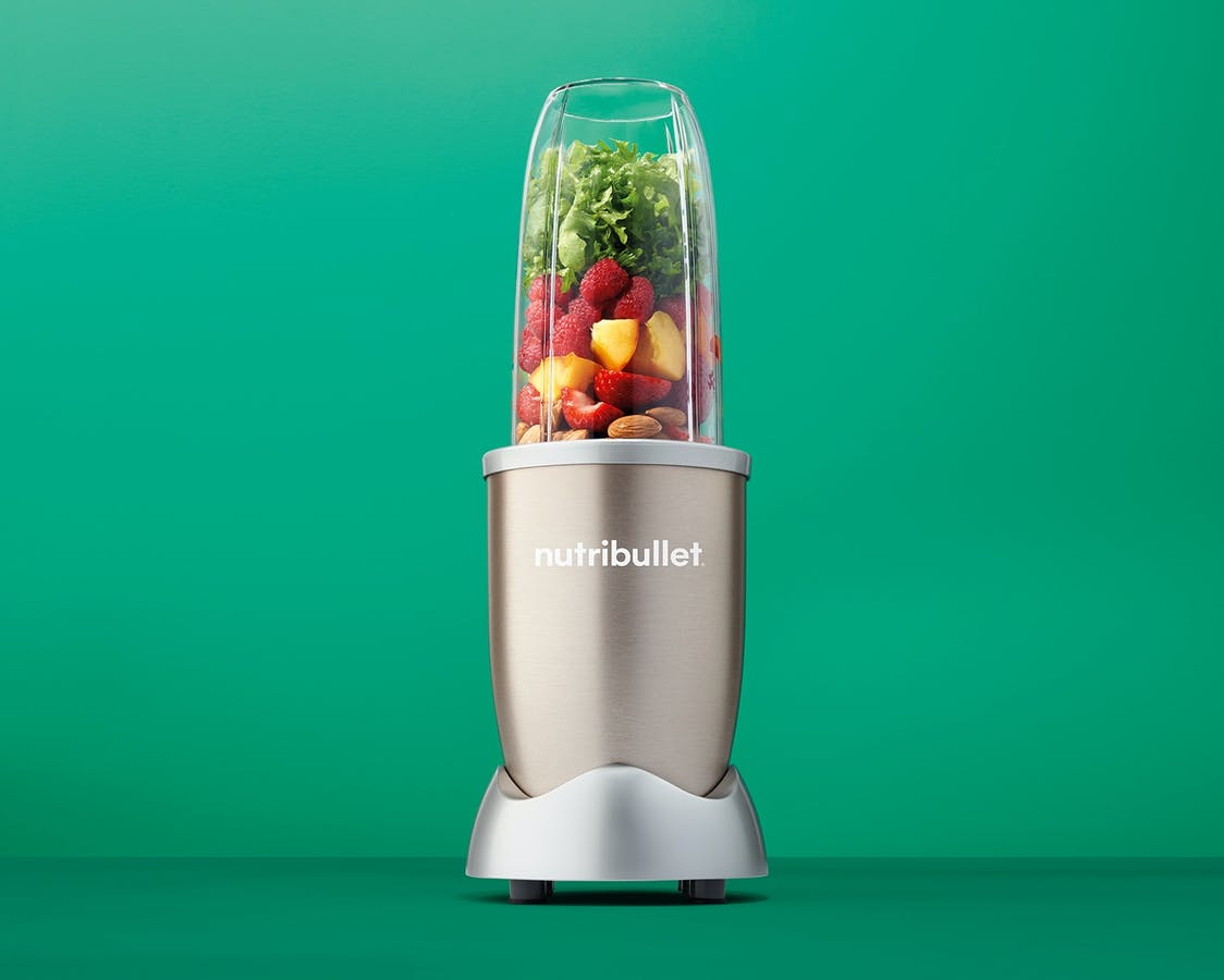 NutriBullet Pro Champagne with fruits, vegetables, and nuts on green background.