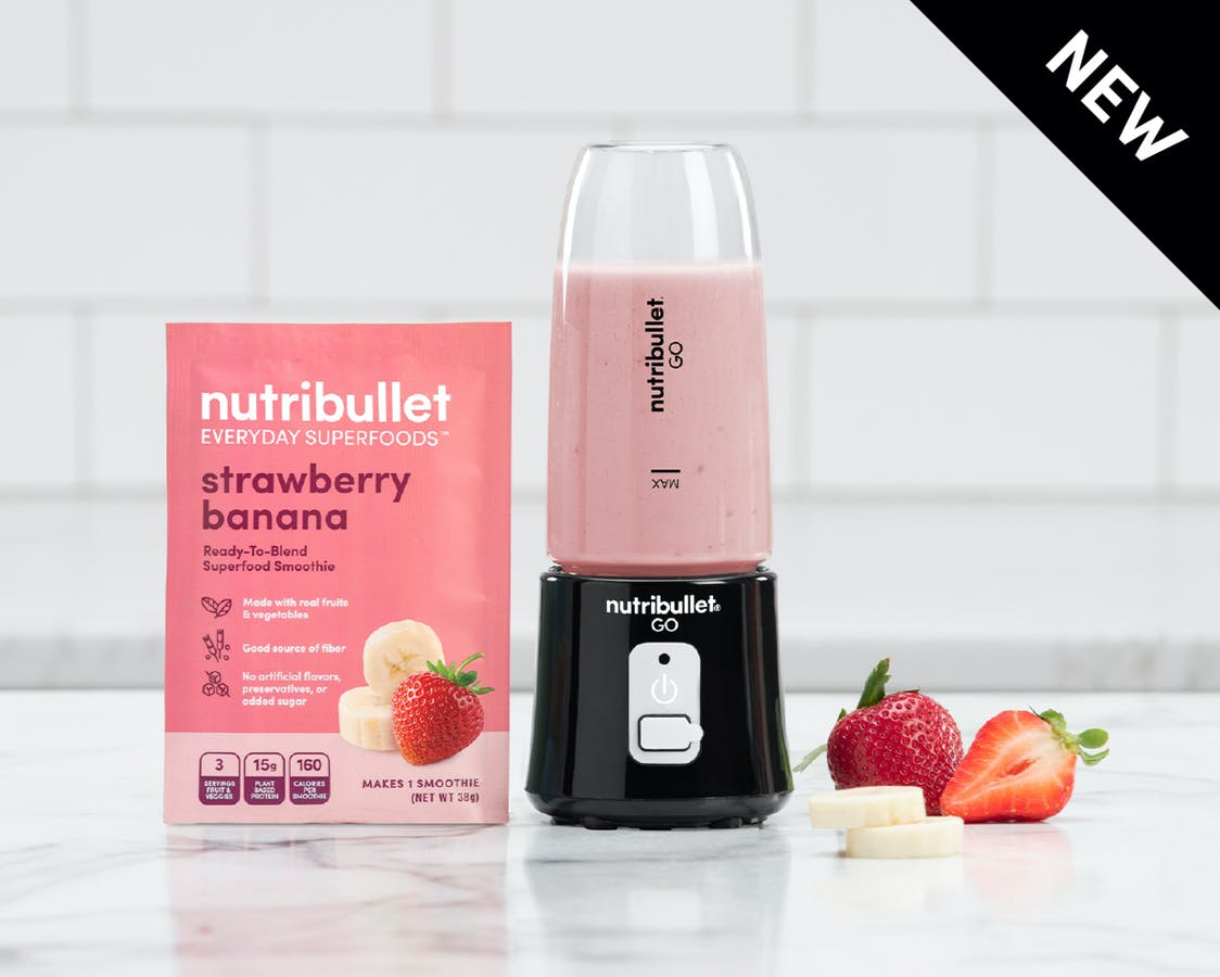 Black NutriBullet Go filled with smoothie and pink strawberry banana smoothie package on counter with strawberry, banana.