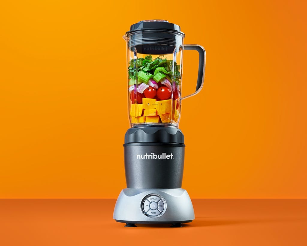 NutriBullet Select with fruits and vegetables on orange background.