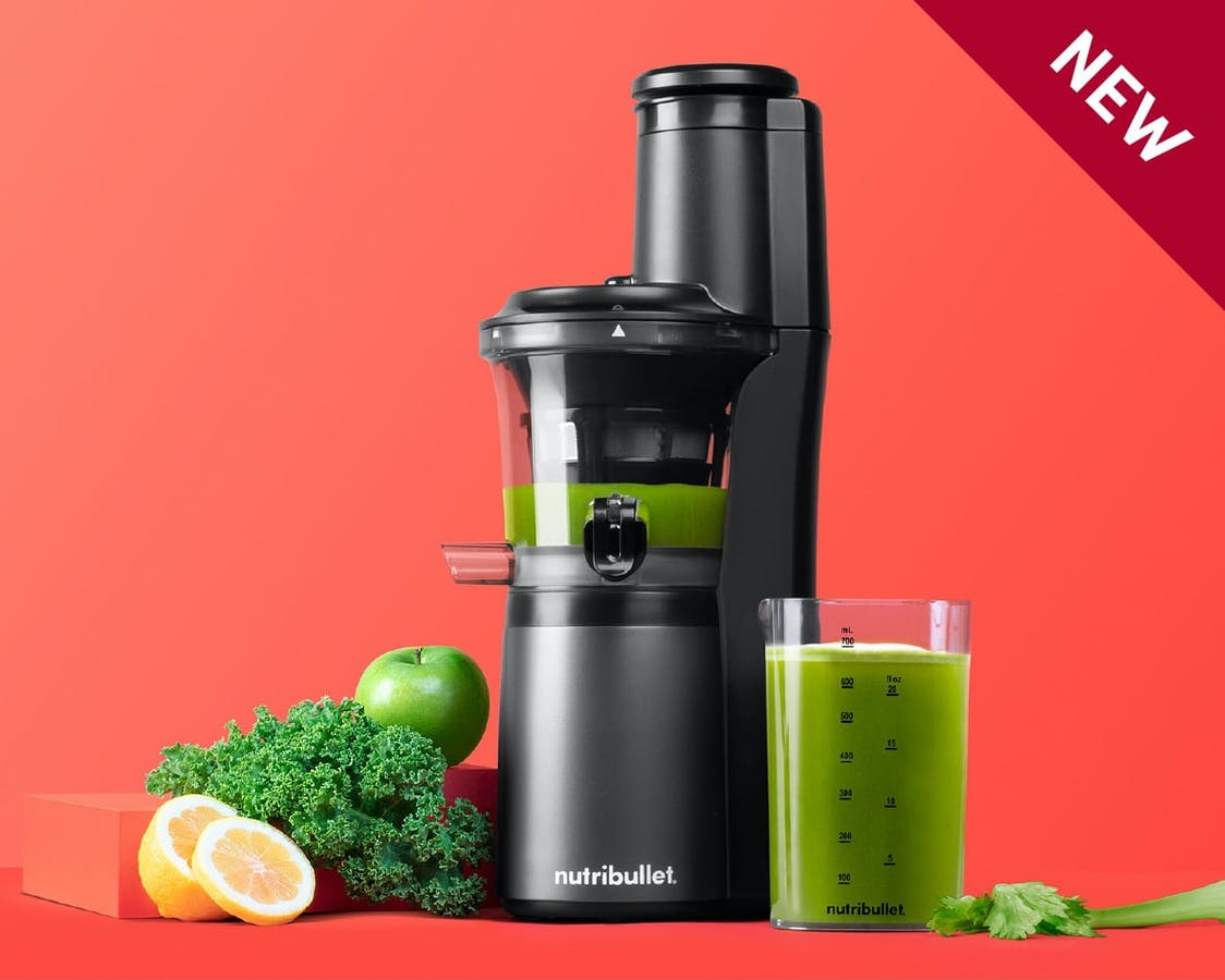 NEW black juicer filled with green juice next to cup of juice, fruits, veggies on orange background.