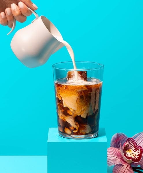 Hand pouring milk into glass of coffee on a pedestal with a flower on a blue background.