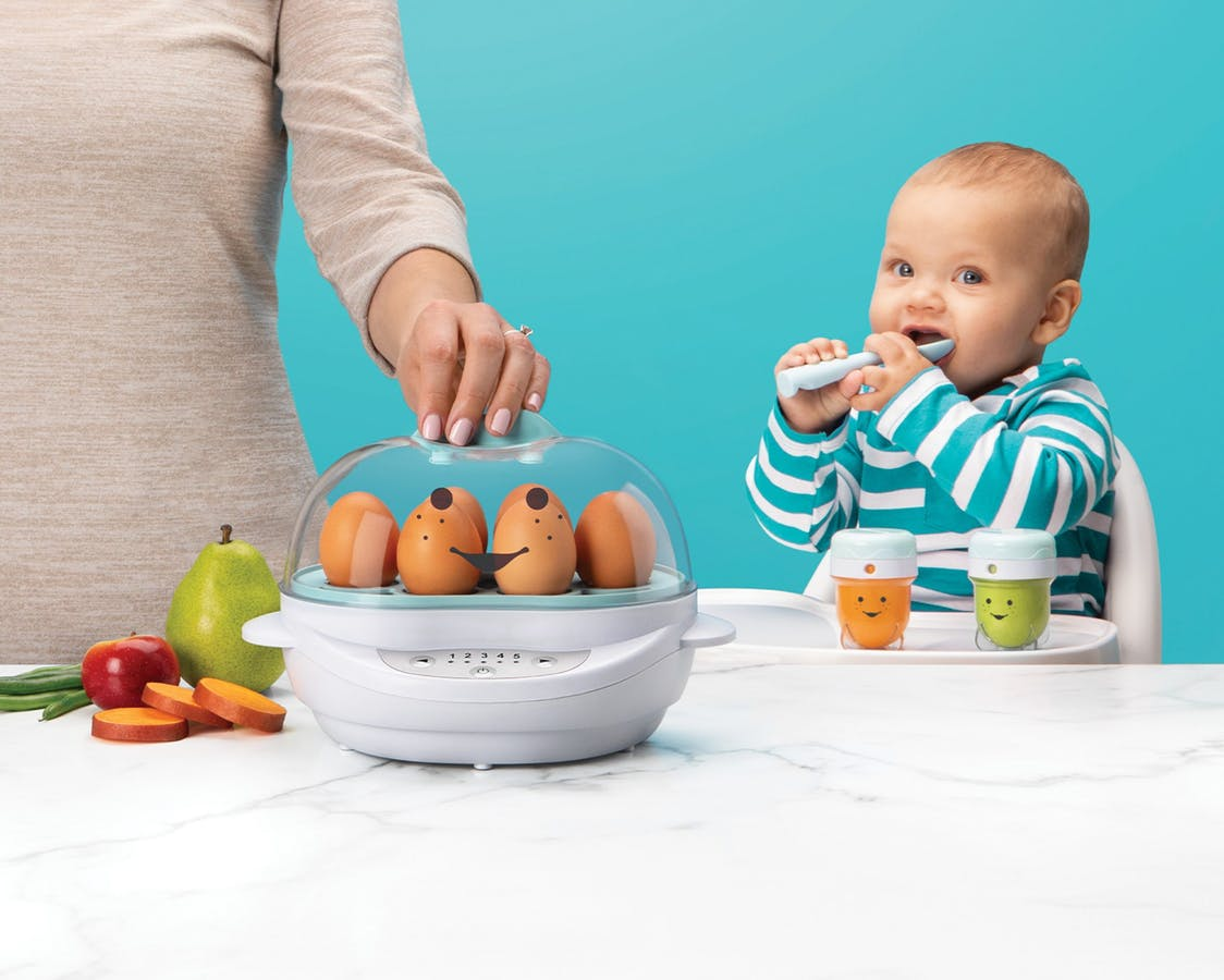 NutriBullet Baby Steamer with eggs next to fruits and veggies with mother's hand and baby eating in background.