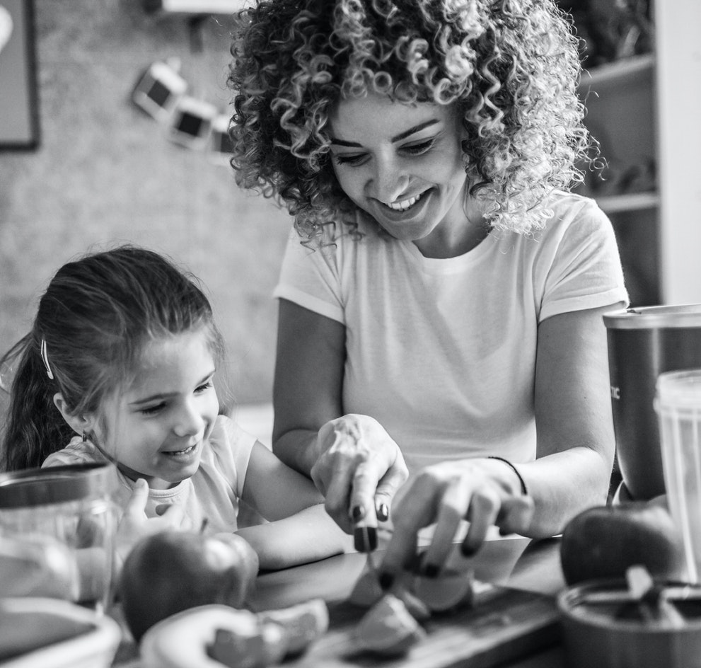 Woman and little girl smiling while slicing fruit in black and white.